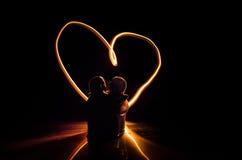 Deux jeunes amants peignent un coeur sur le feu Silhouette des couples et des mots d'amour sur un fond foncé Photo libre de droits