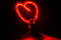 Deux jeunes amants peignent un coeur sur le feu Silhouette des couples et des mots d'amour sur un fond foncé Images stock