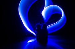 Deux jeunes amants peignent un coeur sur le feu Silhouette des couples et des mots d'amour sur un fond foncé Photos libres de droits