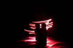 Deux jeunes amants peignent un coeur sur le feu Silhouette des couples et des mots d'amour sur un fond foncé Image stock