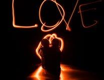 Deux jeunes amants peignent un coeur sur le feu Silhouette des couples et des mots d'amour sur un fond foncé Photographie stock libre de droits
