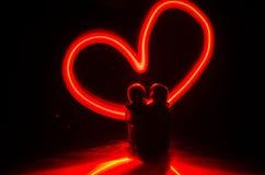 Deux jeunes amants peignent un coeur sur le feu Silhouette des couples et des mots d'amour sur un fond foncé Images libres de droits