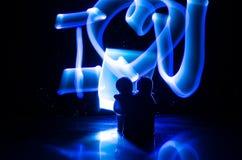 Deux jeunes amants peignent un coeur sur le feu Silhouette des couples et des mots d'amour sur un fond foncé Photographie stock