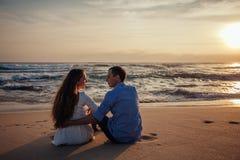 Deux jeunes amants s'asseyant sur une plage et regardant entre eux sur le fond de coucher du soleil Amour de couples de Sillhouet Image stock