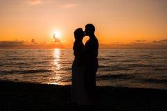 Deux jeunes amants se tenant sur une plage et regardant entre eux Photos libres de droits