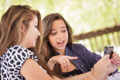 Deux jeunes amies adultes à l'aide de leur téléphone portable intelligent Photographie stock