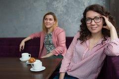 Deux jeunes amies attirantes de femmes boivent du café et s'asseyent sur l'entraîneur photo libre de droits