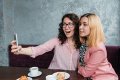 Deux jeunes amies attirantes de femmes prennent le selfie photographie stock
