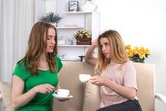 Deux jeunes amies attirantes s'asseyent sur un sofa avec le chapeau du thé Photographie stock