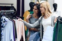 Deux jeunes amies choisissent des vêtements dans le magasin Image libre de droits