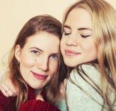Deux jeunes amies dans des chandails d'hiver à l'intérieur Photographie stock libre de droits