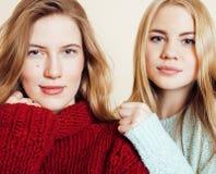 Deux jeunes amies dans des chandails d'hiver ayant à l'intérieur l'amusement lifestyle Haut étroit d'amis de l'adolescence blonds Images libres de droits