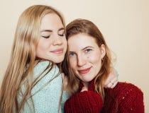 Deux jeunes amies dans des chandails d'hiver ayant à l'intérieur l'amusement lifestyle Haut étroit d'amis de l'adolescence blonds Photos libres de droits
