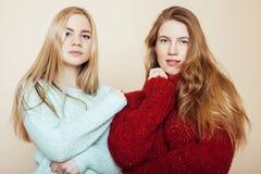 Deux jeunes amies dans des chandails d'hiver ayant à l'intérieur l'amusement lifestyle Haut étroit d'amis de l'adolescence blonds Image libre de droits