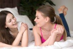 Deux jeunes amies de sourire se trouvant sur le lit et la causerie Photographie stock libre de droits