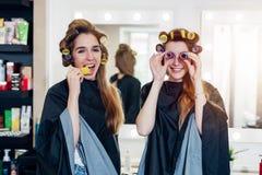 Deux jeunes amies drôles dans des bigoudis de cheveux portant des caps ayant le temps d'amusement ensemble dans le salon de beaut Photos libres de droits