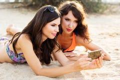 Deux jeunes amies ensemble à la plage Image stock