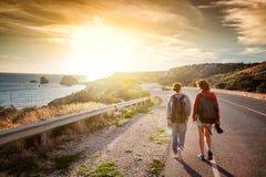 Deux jeunes amies féminines de voyage marchant le long d'une route, aga Photo libre de droits