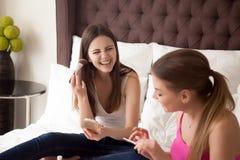 Deux jeunes amies faisant le maquillage et causant dans la chambre à coucher Image stock