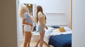 Deux jeunes amies gaies essayant sur des vêtements à la maison banque de vidéos
