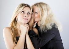 Deux jeunes amies heureuses disant le secret Image stock