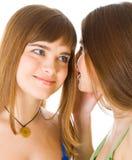 Deux jeunes amies heureuses disant le secret Photographie stock