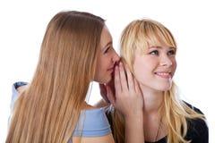 Deux jeunes amies heureuses disant le secret Photographie stock libre de droits