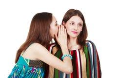Deux jeunes amies heureuses effectuent le bavardage Images stock