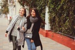 Deux jeunes amies heureuses marchant sur des rues de ville dans des équipements occasionnels de mode Photographie stock