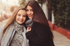 Deux jeunes amies heureuses marchant sur des rues de ville dans des équipements occasionnels de mode Image libre de droits