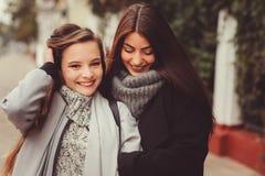 Deux jeunes amies heureuses marchant sur des rues de ville dans des équipements occasionnels de mode Photo stock