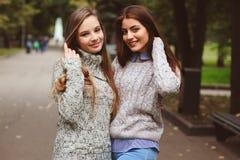 Deux jeunes amies heureuses marchant sur des rues de ville dans des équipements occasionnels de mode Images libres de droits