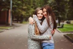Deux jeunes amies heureuses marchant sur des rues de ville dans des équipements occasionnels de mode Photos libres de droits