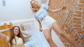 Deux jeunes amies heureuses sautant sur le lit et ayant l'amusement clips vidéos