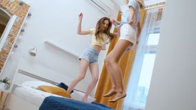 Deux jeunes amies heureuses sautant sur le lit et ayant l'amusement banque de vidéos