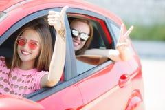 Deux jeunes amies heureuses voyageant dans la voiture Image stock