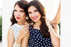 Deux jeunes amies portant les robes intéressantes Image stock