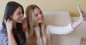 Deux jeunes amies prenant un selfie à la maison Photo libre de droits