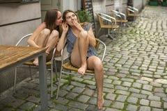 Deux jeunes amies s'asseyant à la table du café et du chuchotement d'extérieur Images libres de droits