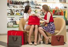 Deux jeunes amies s'asseyant dans la boutique et détendent après shoppi Photos stock