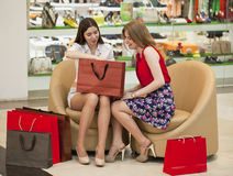 Deux jeunes amies s'asseyant dans la boutique et détendent après shoppi Photo libre de droits