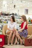 Deux jeunes amies s'asseyant dans la boutique et détendent après shoppi Images libres de droits