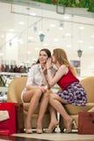 Deux jeunes amies s'asseyant dans la boutique et détendent après shoppi Photographie stock