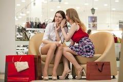 Deux jeunes amies s'asseyant dans la boutique et détendent après shoppi Photo stock
