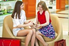 Deux jeunes amies s'asseyant dans la boutique et détendent après shoppi Photographie stock libre de droits