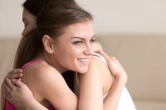 Deux jeunes amies s'embrassant, fille souriant heureusement Images stock