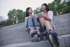 Deux jeunes amis avec des lames de rouleau se reposant et se reposant sur des pas concrets dehors Photographie stock libre de droits