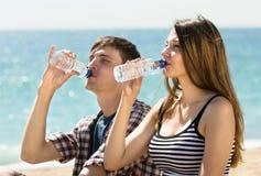 Deux jeunes amis buvant l'eau en bouteille Photographie stock