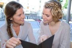 Deux jeunes amis caucasiens de femmes se réunissant au café local Image libre de droits