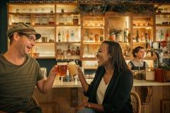 Deux jeunes amis de sourire encourageant avec des boissons dans une barre Image stock